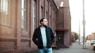 Medium shot portrait of bearded European man. Male in leather jacket looks left, hesitating, nervous. Red brick wall 4K.