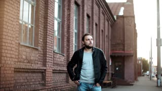 Medium shot portrait of casual European man. Relaxed young male in leather jacket stands waiting. Red brick building 4K.