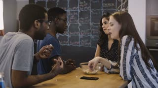Mixed ethnicity friends chat by a table together. Office open space kitchen. Diverse employees talk and eat snacks. 4K