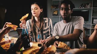 Mixed ethnicity group of happy young friends eating pizza and having drinks at a casual house party by kitchen bar table