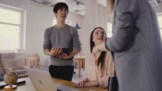 Mixed race colleagues talk to female boss. Happy millennial workers smile and meet CEO in light trendy office space 4K.