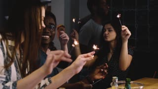 Mixed race young people dance with Bengal lights. Slow motion. Birthday celebration house party. Happiness emotion.