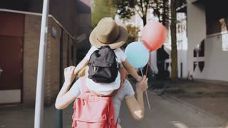 Mom with son on shoulders walk holding hands. Happy woman carries a kid in hat and two air balloons. Lifestyle 4K.