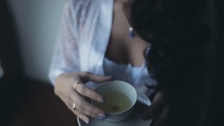 Morning of young beautiful bride. Close-up view of woman in lingerie, peignoir staying near window and drinking tea.