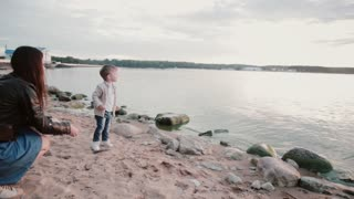 Mother and son on the shore on sunset. Boy throws stone into the water. Male turns, fall down and show mammy the hand.