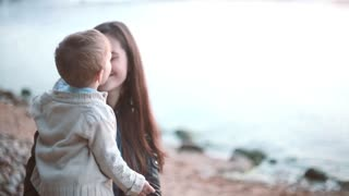 Mother and son spending time together on the shore of the beach. Boy kisses on the nose, happy woman laughing.