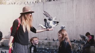 Mother and two kids feed pigeons on hands. Birds sit on happy woman's hand and eat. Slow motion. Family vacation.