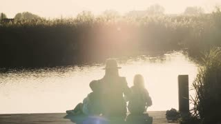 Mother and two kids sit on lake pier at sunrise. Peace and harmony. Family bonding time. Amazing warm lens flare. 4K.