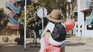 Mother carries son on shoulders among houses. Woman walking with a kid in hat and two air balloons. Lifestyle 4K.