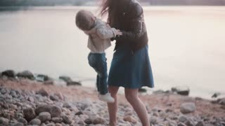 Mother holding son on her hand on the shore of the beach. Smiling woman pick up her little boy, kiss and hug