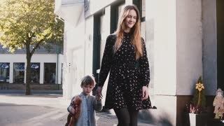 Mother walks together with little boy. Holding hands. Slow motion. Pretty European woman spends time with kid. Vacation.