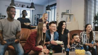 Multi-ethnic friends watching TV show. Medium shot. Diverse team supporters passionate and cheerful. 4K slow motion.