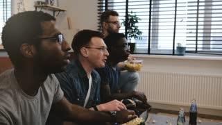 Multi ethnic guys watch sports on TV eat popcorn. 4K close-up slow motion side view. Male fans supporters celebrate goal