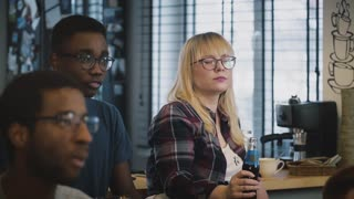 Multi-ethnic serious students at a meeting. Slow motion. Serious Caucasian girl in glasses listens carefully with drink