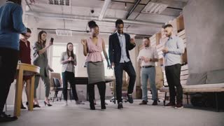 Multiethnic business people celebrate business achievement at casual office dance party in modern coworking slow motion.