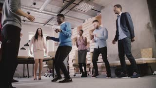 Multiethnic business people celebrate business sucess at teambuilding casual dance party in modern office slow motion.