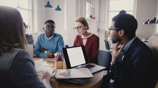 Multiethnic business people talk at office meeting. Happy millennial startup partners negotiate business agreement 4K.