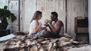 Multiethnic couple in pajamas sitting on the bed and twist the globe, choose the destination to traveling together.
