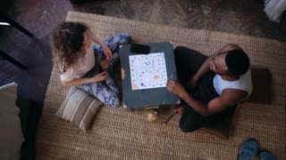 Multiethnic couple in pajamas sitting on the floor and playing the board game. Man and woman laugh and show the monkey.