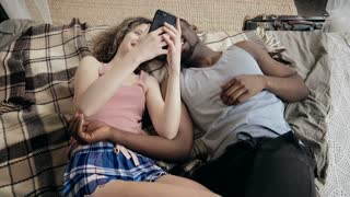 Multiethnic couple lying on bed and using smartphone. Man and woman happy together. Male and female laughing, smiling.
