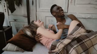 Multiethnic couple lying on bed, la holding their hands. Male and female look happy. Man and woman enjoy time together.