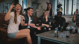 Multiethnic friends congratulate Caucasian shy birthday girl with sparkling firework cake at surprise party slow motion.