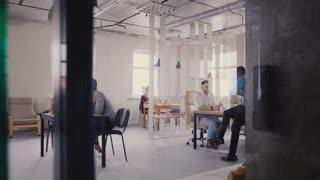 Multiethnic team working in modern trendy office. Happy young smiling creative millennials work in light coworking 4K.