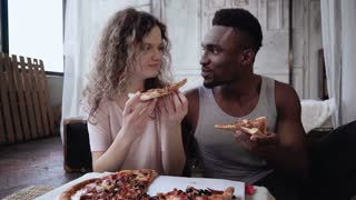 Multiracial couple have fun during the meal. Woman feed the man a slice of pizza. Male and female eating fast food.