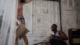 Multiracial couple have fun in the morning. Man and woman in pajamas have fight with pillows. Slow motion.