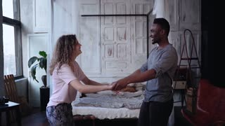 Multiracial couple in pajamas dancing, having fun together in morning. Woman jumps on man hands, kisses. Slow motion.