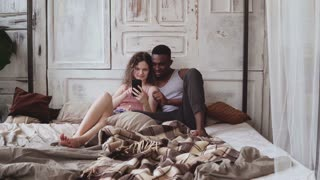 Multiracial couple in pajamas sitting on bed and use smartphone. African man and european woman looking photos, laughing