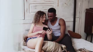 Multiracial couple in pajamas sitting on bed and use smartphone. African man and european woman surf the Internet, smile