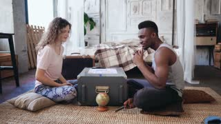 Multiracial couple in pajamas sitting on the floor and playing the boar game. Woman throws the dice, man waits his turn.