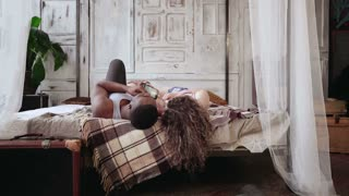 Multiracial couple lying on bed, listening music on smartphone. Man and woman in pajamas have rest together in morning.