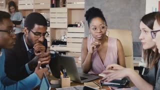 Multiracial creative team work on financial report. Young diverse employees develop company plans at office meeting 4K.