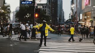 NEW YORK AUG 18 2017 - African American traffic control policeman directing traffic cars flow on busy street in New York