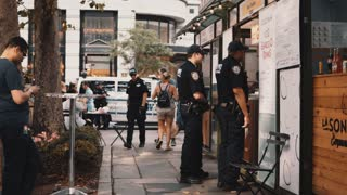 NEW YORK, USA, 18. 08. 2017 Street food market. Mans from New York police department buying coffee or snack in open shop.