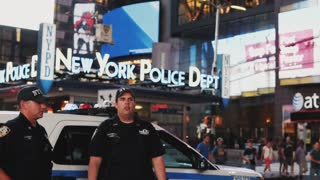 NEW YORK, USA, 18. 08. 2017 Two policeman stand on Time square in New York, America and talking, looking on traffic road