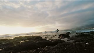 Panorama view to sunset on beach. Surfer holding a surfboard and coming into the water. Beautiful seascape.