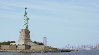Panoramic view of world famous Statue of Liberty with crowd of tourists and New York City in background, view from water