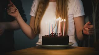 People dancing around birthday cake with candles. Friends celebrate together. Girl in white shirt holds a pie. Party. 4K