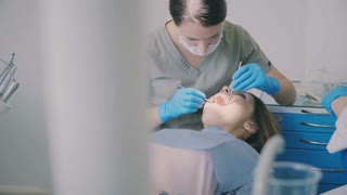 Planned dental check-up. Woman sitting in dentist chair with open mouth while the doctor treats the patient.
