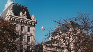 Police prefecture building in Paris, France. French flag flying in blue sky on sunny day. Historic European landmark. 4K