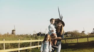Portrait of a European family near windmill farm. Beautiful woman in hat with little boy and girl walk together. 4K.