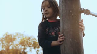 Portrait of adorable little girl on ropes course. Happy smiling female kid walk over playground obstacles. Panning shot.