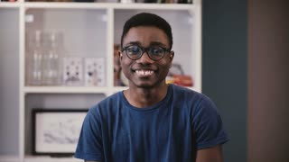 Portrait of African American college student. Happy black young guy in glasses smiles, then becomes serious. Emotions 4K