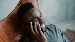 Portrait of African man sitting in chair in a bright room and talking on the Smartphone. Man laughing and having fun.