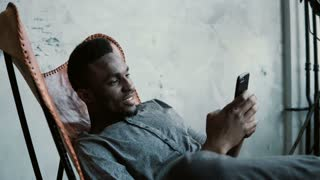 Portrait of African man sitting in chair, using a Smartphone. Handsome male smiles and looks at photos in his phone.