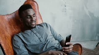 Portrait of African man sitting in chair, using Smartphone. Man reads messages and laughs. Guy typing massages, smiling
