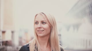 Portrait of beautiful blonde girl looking at camera and smiling. Young attractive woman on the blur city background.